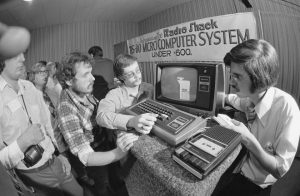 Radio Shack's Micro Computer System, uses their computer keyboard into regular home TV set and programmed by tape cassette on home cassette player at Boston Computer show on August 25, 1977. Left to right: visitors Robert Lundgren of Des Plaines, Ill.; Malcolm MacLeod of Montreal; and Radio Shack salesman Steven Carlozzi of Brockton, Mass. (AP Photo/CM)